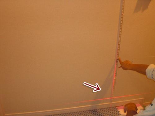 【2】レーザーで垂直を見ながら、見切り材を取り付ける。